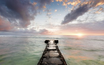 Cement pier extending to horizon at sunset